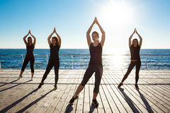 Siluette delle ragazze allegre che ballano zumba vicino al mare all'alba Fotografia Stock