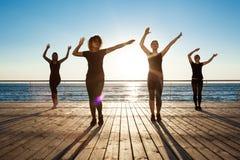 Siluette delle ragazze allegre che ballano zumba vicino al mare all'alba Immagine Stock