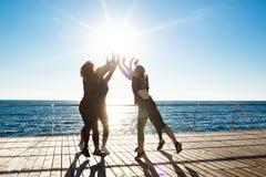 Siluette delle ragazze allegre che danno mare vicino highfive all'alba Fotografie Stock