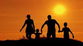 Siluette di funzionamento felice della famiglia su un fondo di tramonto archivi video