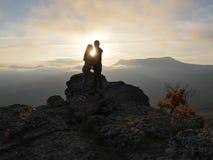 Siluette di giovani coppie che stanno su una montagna e che guardano l'un l'altro sul bello fondo di tramonto Amore del tipo Fotografie Stock