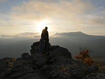 Siluette di giovani coppie che stanno su una montagna e che guardano l'un l'altro sul bello fondo di tramonto Amore del tipo Immagini Stock Libere da Diritti
