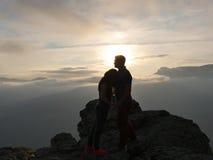 Siluette di giovani coppie che stanno su una montagna e che guardano l'un l'altro sul bello fondo di tramonto Amore del tipo Fotografia Stock