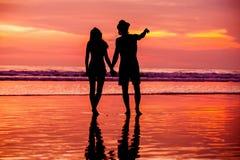 Siluette di giovani coppie nell'amore che staing sul Fotografie Stock Libere da Diritti