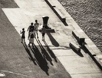 Siluette di un gruppo di persone che gettano le ombre lunghe su un asph fotografia stock