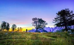Siluette di un uomo e di una tenda illuminata sotto un cielo notturno all'ora crepuscolare Alpi, parco nazionale di Triglav, Slov Fotografie Stock