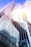 Siluette di vetro moderne dei grattacieli nella città e nella luce solare drammatica Immagine Stock