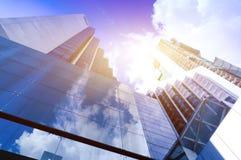 Siluette di vetro moderne dei grattacieli nella città e nella luce solare drammatica Fotografia Stock