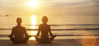 Siluette di yoga della donna e dell'uomo che meditano su costa di mare Fotografia Stock