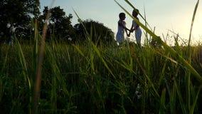 Siluette, figure dei bambini, ragazzo e ragazza che saltano, divertiresi, ballante contro lo sfondo del sole, al tramonto stock footage