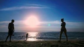 siluette la gente gioca il volano sulla spiaggia al tramonto archivi video
