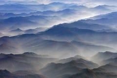 Siluette luminose delle catene di montagna ad alba, fotografate da un aeroplano: diagonali delle valli blu e marroni della montag Fotografia Stock