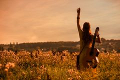 Free Siluette Of Woman Wearing A Bohemian Style Holding A Guitar On A Field At Sunset Royalty Free Stock Photos - 160107388