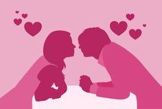 Siluette romantiche di seduta di colore di rosa della data di bacio della Tabella del caffè delle coppie Fotografia Stock