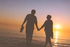 Siluette senior felici delle coppie sulla spiaggia fotografia stock libera da diritti