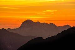 Siluette spettacolari delle montagne nella penombra arancio di tramonto Alpi di Julian, Slovenia Immagini Stock Libere da Diritti