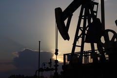 Siluette van de post van de Oliepomp in zonsondergang Tansport en distributie van olie Technologie van het systeem van het olieve royalty-vrije stock afbeeldingen