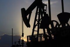 Siluette van de post van de Oliepomp in zonsondergang Tansport en distributie van olie Technologie van het systeem van het olieve stock foto's