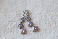 Silverörhängen med violetta ädelstenar arkivfoton