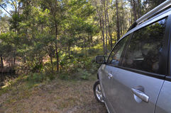 A silver 4WD car facing bushland area Stock Photos