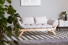 Silver abstract painting on wall above scandinavian futon stock photo