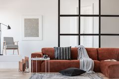 Silver abstract painting in white frame on the wall of trendy living room interior with brown corner sofa royalty free stock images
