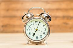 Silver alarm clock in retro style on a wooden background close-up. Shows 7 am stock image