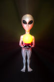 Silver alien. Hold a lamp over black background Stock Photo