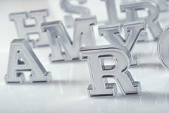 Silver alphabet letters close-up on a white royalty free stock images