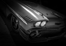 Silver American Muscle Retro Car. Silver american muscle classic car using monochrome on black background with black grill and headlight and black rims Stock Images