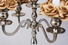 Silver ancient candelabrum. Close up of a silver candelabrum with blurred golden roses Royalty Free Stock Photography