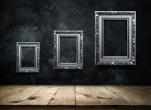 Silver Antique picture Frame on dark grunge wall with Wooden tab Stock Photo