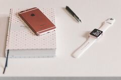 Silver Apple Watch White Sports Band Near Rose Gold Iphone 6 on White Wooden Table Stock Photo