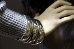 Silver arm bracelets and woollen sweater. Silver arm bracelets and purple woollen designer sweater on display by a mannequin Royalty Free Stock Images