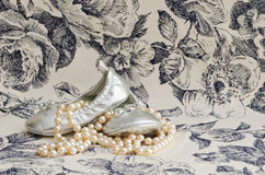 Silver baby slippers and pearls Royalty Free Stock Photos