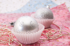 Silver ball christmas ornaments. In paper cups with gold beads on blue and pink background Stock Images