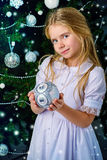 Silver ball. Happy little girl in a beautiful white dress decorates the Christmas tree. Merry Christmas Stock Photos