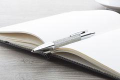 Silver ball pen with leather notebook. Stock Photos