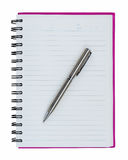 Silver ball point pen on pink notebook Royalty Free Stock Photo