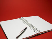 Silver ball point pen on white sketchbook with red background Royalty Free Stock Photos