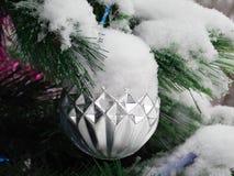 Silver ball on snowy pine tree. Beautiful ribbed plastic ball on snowy Christmas tree Royalty Free Stock Photo