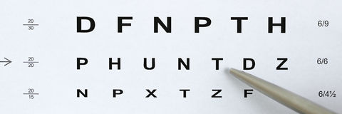Silver ballpoint pen pointing to letter in eyesight check table Royalty Free Stock Photos