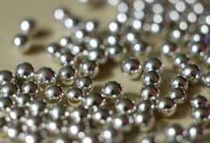 Silver balls 2. Tiny silver balls on a tabletop royalty free stock photo