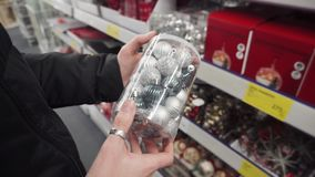 Silver balls for the Christmas tree in female hands. Preparation for the New Year holidays, selection of New Year`s