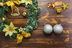 Silver balls, golden bells, Christmas wreath set on wooden texture royalty free stock image