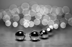 Silver balls from the New Year Christmas garland lying on a table on the background of blurred gerlyani with beautiful bokeh and. Reflection. Black and white royalty free stock photography