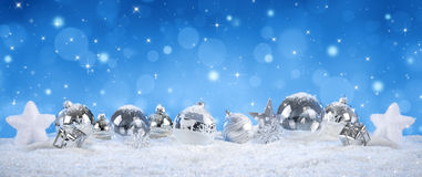 Silver balls on snow with snowfall. Blue heaven stock photo