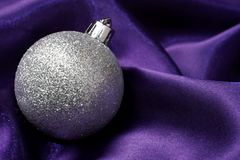 Silver bauble on purple cloth Royalty Free Stock Photo