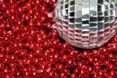 Silver Bauble red beads. Silver Bauble over pile of red beads Royalty Free Stock Photos
