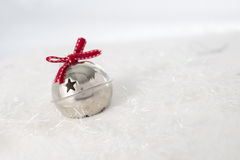 Silver bauble with red bow. On snow Royalty Free Stock Photo